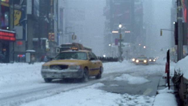 2003 medium shot vehicles driving through Times Square during blizzard / New York City