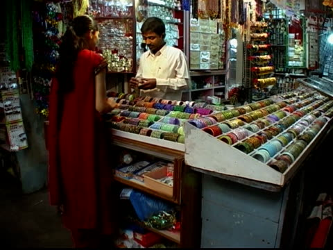 Medium shot vendor helping woman try on bangles at jewelry market stall