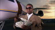 Medium shot Wealthy businessman counting money and holding cigar near private airplane / Long Beach, California, USA