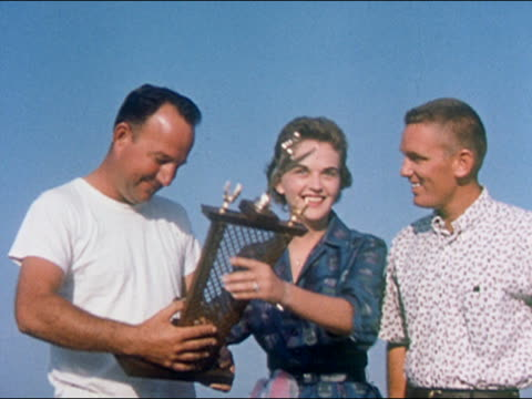 1959 medium shot winners receiving trophies / woman kissing first man on cheek, second man on mouth