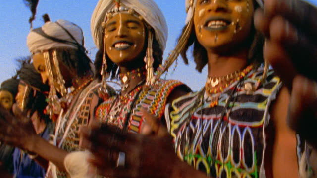 Medium shot Wodaabe people in traditional dress and face paint clapping at outdoor wedding / Niger