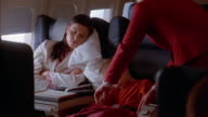 Medium shot woman and young boy sleeping on airplane / flight attendant pulling blanket around boy