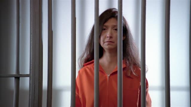 Medium shot woman behind prison bars looking at camera and looking sad