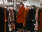 1971 medium shot woman buttoning up 3/4 length red jacket in coat room / spinning around to model coat