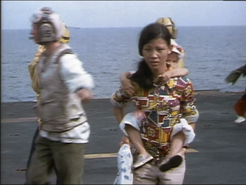 1975 medium shot woman carrying child on her back and other Saigon evacuees aboard US carrier ship