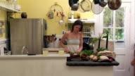 Medium shot woman cutting vegetables in kitchen/ man walking in and kissing her/ pan man sitting on counter/ Roxbury, New York