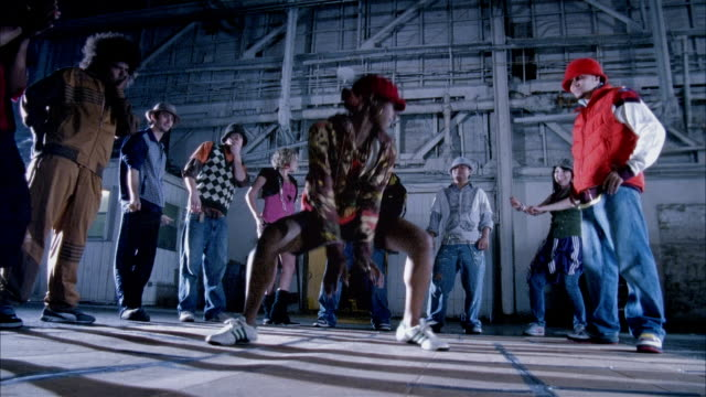 Medium shot woman dancing suggestively in warehouse as people watch