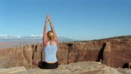 Medium shot woman doing yoga on edge of canyon with mountains in background / Canyonlands National Park, Utah