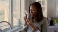 Medium shot woman drinking from mug in kitchen/ Solebury, Pennsylvania