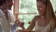 Medium shot woman feeding man omelette / man feeding woman and two boys