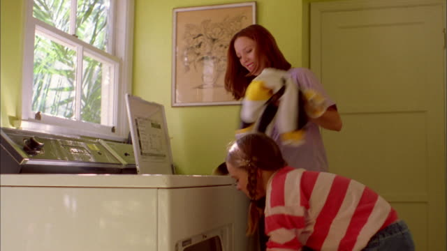 Medium shot woman handing clothes from washer to young girl / girl loading clothes into dryer
