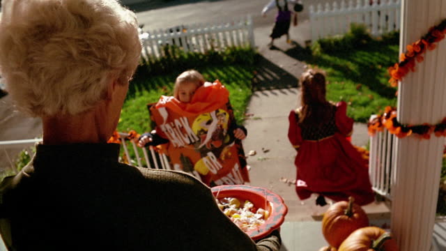 Medium shot woman holding bowl of candy as young children in costume come to door / Pennsylvania