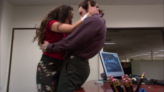 Medium shot woman kissing man in office / pushing him onto desk and climbing on top / kissing on desk / low angle