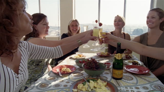 Medium shot woman making champagne toast at brunch table/ San Francisco, California
