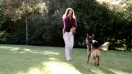 Medium shot woman playing fetch with German shepherd in yard