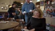 Medium shot woman reading book at cafe / man bringing coffee to woman and sitting down at next table