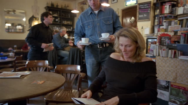 Medium shot woman reading book at cafe / man bringing coffee to woman and sitting down at next table