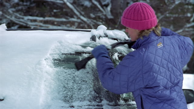 Medium shot woman scraping snow and ice off windshield / Vermont