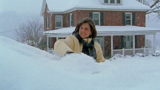 Medium shot woman scraping snow off car / house in background