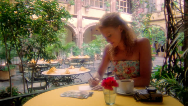 Medium shot woman sitting at cafe writing postcards / smiling at CAM