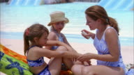 Medium shot woman spraying sunscreen on young girls / water in background