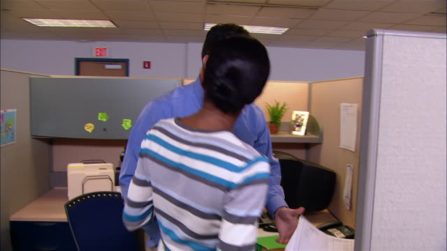 Medium shot woman storming into man's cubicle and arguing / man being handed file and reassuring woman