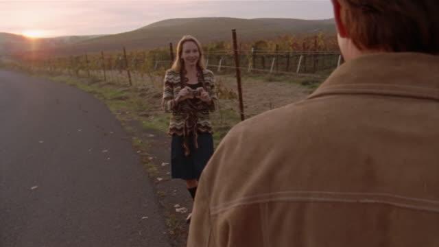 Medium shot woman taking photo of man on roadside next to vineyard/ Napa Valley, California
