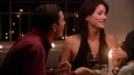Medium shot woman talking excitedly while man eats at dinner party