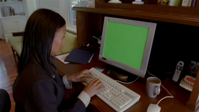 Medium shot woman typing on PC with green screen on monitor/ Solebury, Pennsylvania