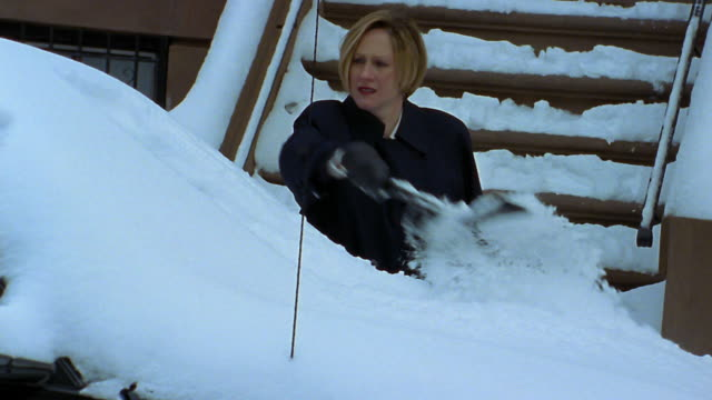 Medium shot woman using brush to clean snow off car windshield / Brownstone steps in background