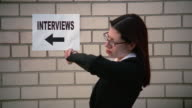 Medium shot woman waiting by brick wall for job interview and looking around