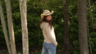 Medium shot woman wearing straw cowboy hat standing with back to the camera / looking  over shoulder at camera and removing hat