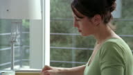 Medium shot woman writing in journal or composing letter at desk by window / pausing and thinking