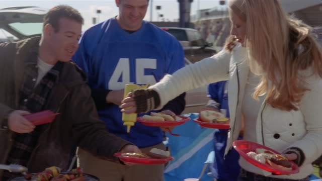 Medium shot women squirting mustard on men's plates at tailgate party/ Connecticut