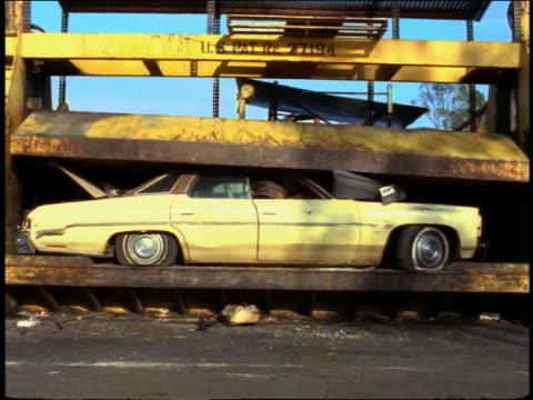 Medium shot yellow car being crushed by compactor in junkyard w/windows shattering