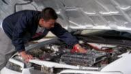 Medium shot young Asian man examining car engine w/hood open / looking toward CAM and smiling / California