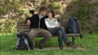Medium shot young backpacking couple sitting on bench and resting / man pulling guidebook out of bag