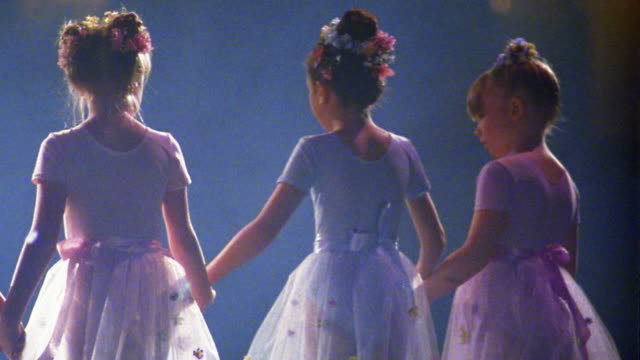 Medium shot young ballerinas wearing tutus holding hands and bowing / looking up +  walking away