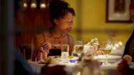 Medium shot young Black couple eating dinner and talking w/glasses of wine , food + water on table