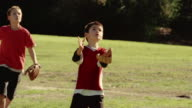 Medium shot young boy catching baseball as girl runs by in background / team celebrating catch