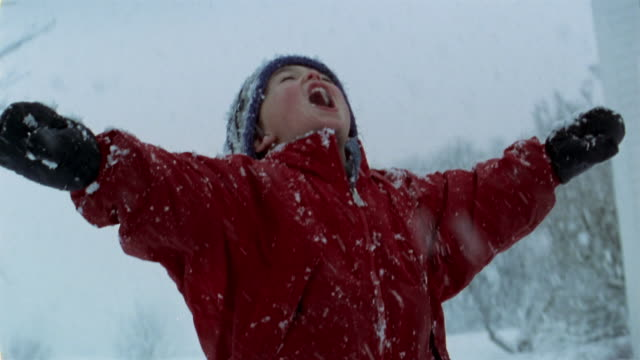 Medium shot young boy looking up at sky and catching snowflakes on his tongue