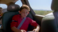 Medium shot young boy sitting in backseat of minivan and playing video game