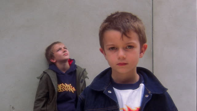 Medium shot young boy standing and looking at CAM in foreground / boy standing against wall in background looking up at sky
