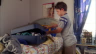 Medium shot young boy trying to close stuffed suitcase on top of bed