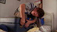 Medium shot young boy trying to close stuffed suitcase w/knee on lid