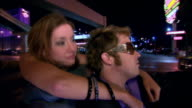 Medium shot Young couple driving in convertible in city at night/ Las Vegas, Nevada, USA