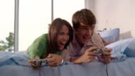 Medium shot young couple playing video game on bed / woman winning game / South Africa