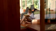 Medium shot. Young couple reading in bedroom.