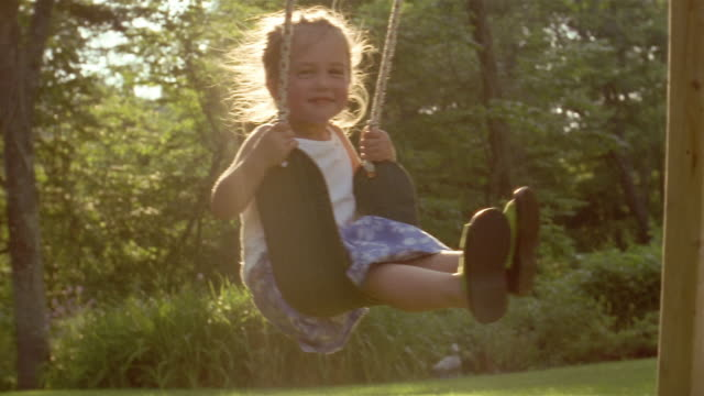 Medium shot young girl on swing on sunny afternoon