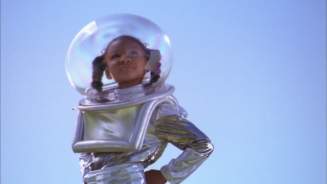 Medium shot young girl posing outdoors in silver astronaut costume and helmet